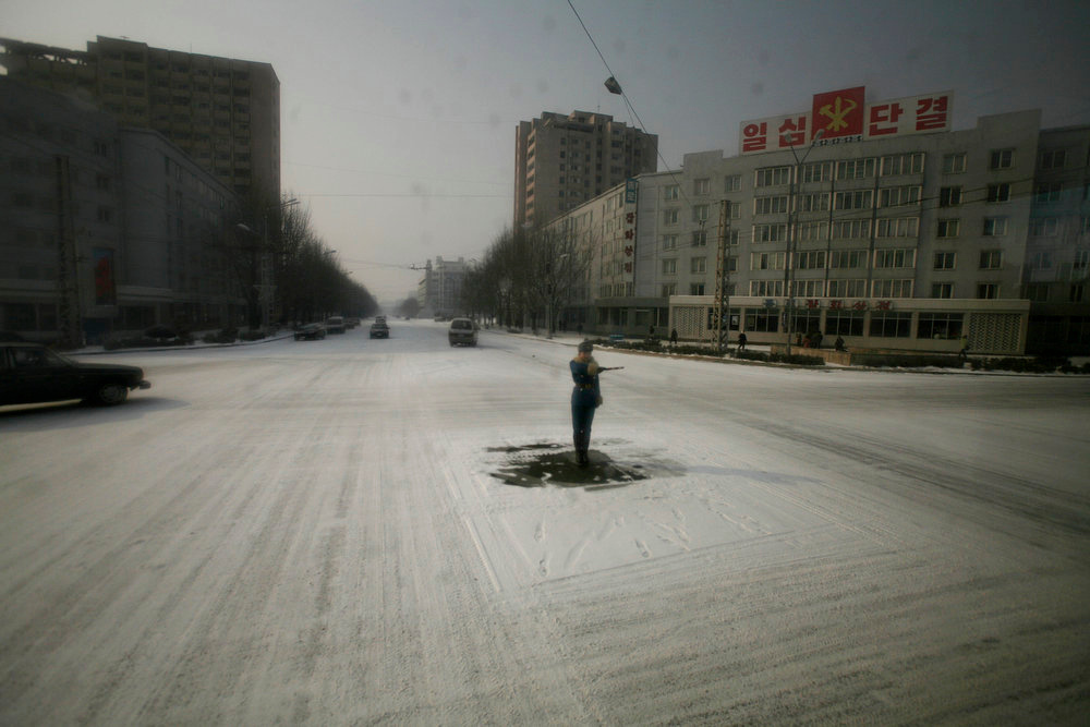 Description of . A traffic guard stands in the center of a snowy street in Pyongyang, North Korea on Tuesday, Feb. 26, 2008.  (AP Photo/David Guttenfelder)