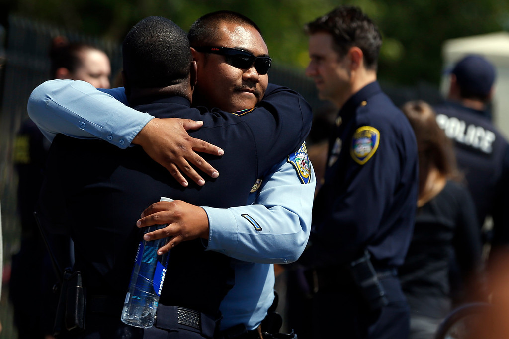 . Union City police Chief Darryl McAllister, left, is comforted by fellow officers after the police ceremonial procession of the body of Hayward police Sgt. Scott Lunger from the Coroner\'s Bureau in Oakland to Chapel of the Chimes Memorial Park in Hayward, Calif., on Thursday, July 23, 2015. McAllister worked for Hayward Police Department for 32 years where he knew Lunger, who was killed during a traffic stop in early Wednesday. (Ray Chavez/Bay Area News Group)