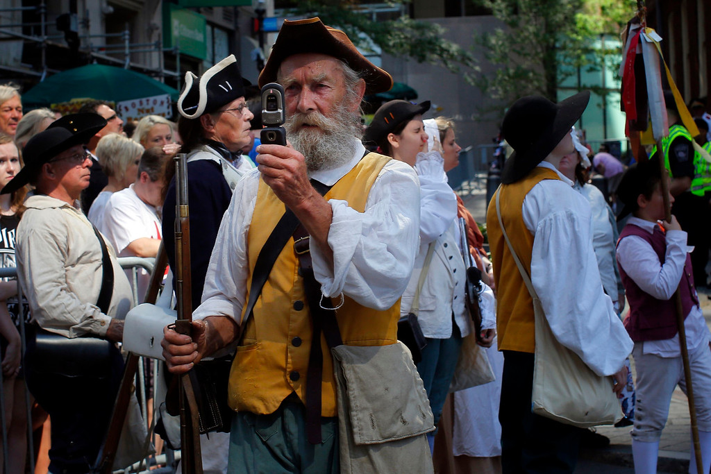 . A re-enactor in period attire takes a photograph with his mobile phone before a public reading the United States Declaration of Independence, part of Fourth of July Independence Day celebrations, in Boston, Massachusetts July 4, 2013. People across the United States gathered on Thursday for parades, picnics and fireworks at Independence Day celebrations, held under unprecedented security following the Boston Marathon bombings. Spectators waving U.S. flags and wearing red, white and blue headed for public gatherings in Boston, New York, Washington, Atlanta and other cities under the close watch of police armed with hand-held chemical detectors, radiation scanners and camera surveillance, precautions sparked by the deadly April 15 bombings.     REUTERS/Brian Snyder