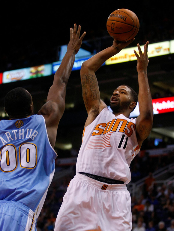 . Phoenix Suns power forward Markieff Morris (11), right, scores over the top of Denver Nuggets power forward Darrell Arthur (00) in the third quarter during an NBA basketball game on Friday, Nov. 8, 2013, in Phoenix. The Suns defeated the Nuggets 114-93. (AP Photo/Rick Scuteri)