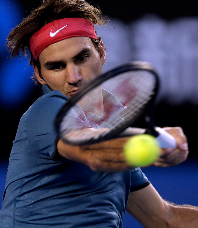 . Roger Federer of Switzerland makes a forehand return to Rafael Nadal of Spain during their semifinal at the Australian Open tennis championship in Melbourne, Australia, Friday, Jan. 24, 2014.(AP Photo/Rick Rycroft)