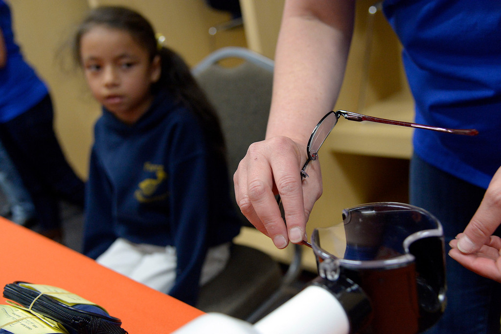 . Eileen Viapando heats up the frames for fitting as Monsserat Jimenez Keria, 8, waits for her prescription glasses April 14, 2014. Miller\'s Foundation, Von\'sVision, distributed prescription glasses to more than 100 underprivileged children at Sports Authority Field. (Photo by John Leyba/The Denver Post)