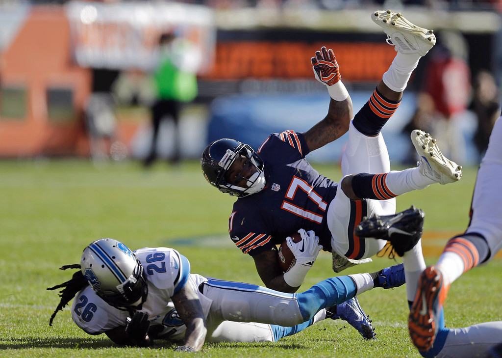 . Chicago Bears wide receiver Alshon Jeffery (17) trips over Detroit Lions safety Louis Delmas (26) after making a reception during the first half of an NFL football game, Sunday, Nov. 10, 2013, in Chicago. (AP Photo/Nam Y. Huh)
