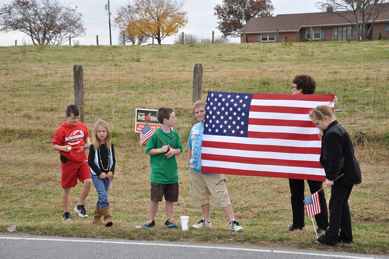 Local family hold the flag in honor of Sgt. Newman