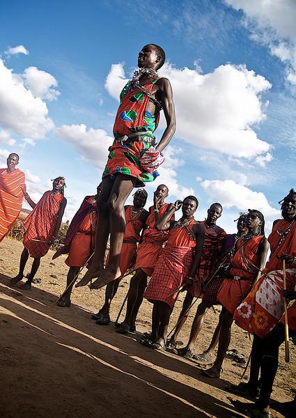 Jumping Jack Flash. Masaishow for besøkende turister, men også en helt vanlig fritidsaktivitet. Den som hopper høyest får dama. Masai Mara, oktober 2006. *** Jumping Jack Flash. Masais showing off for their tourist visitors, although this is one way for Masaii males to hang out after a day's work. The highest jumper gets the lady. Masai Mara, October 2006. (Foto: Geir)