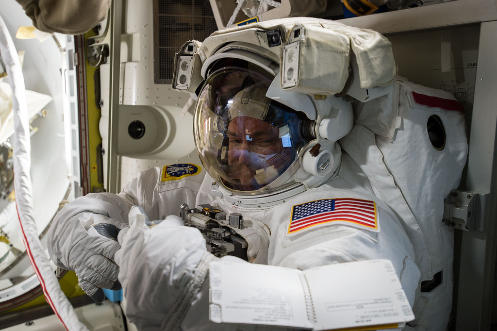 . In this Oct. 22, 2015 photo, Expedition 45 Commander Scott Kelly tries on his spacesuit inside the U.S. Quest airlock of the International Space Station. (NASA via AP)