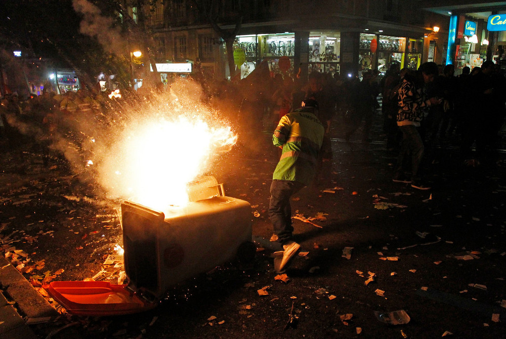 . A protestor steps away from burning trash as fireworks explode during a demonstration against layoffs of street cleaners and garbage collectors in Madrid, Spain, Monday, Nov. 4, 2013. Trash collectors in Madrid have started bonfires and set off firecrackers during a noisy protest in one of the Spanish capitalís main squares as they prepare to start an open-ended strike.Hundreds of street cleaners and garbage collectors who work in the cityís public parks converged on the Puerta del Sol plaza late Monday. (AP Photo/Francisco Seco)