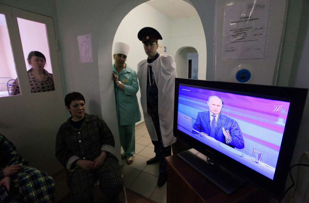 . Female inmates, a member of the medical staff (2nd R) and a penitentiary officer (R) watch a live broadcast of a nationwide phone-in with Russian President Vladimir Putin in the tubercular hospital of a prison in Russia\'s Siberian city of Krasnoyarsk April 25, 2013.  Putin said on Thursday the Boston bombings showed the need for Russia and the United States to work more closely on security matters and proved his policy on the restive North Caucasus region was correct.  REUTERS/Ilya Naymushin