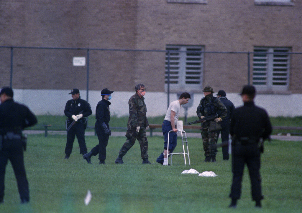 . An inmate using a walker is escorted from the Southern Ohio Correctional Facility in Lucasville, where inmates holding five guards hostage have ended their 10-day siege, April 21, 1993. (AP Photo/Lennox McLendon/Pool)