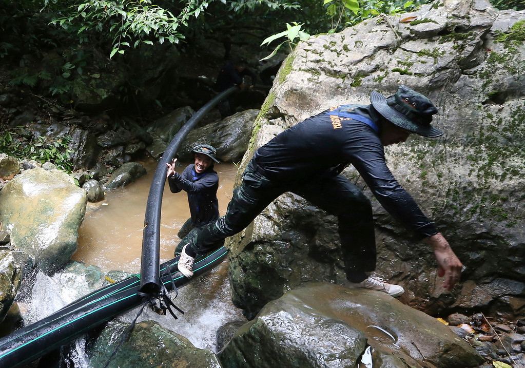 . Thai soldiers drag a water pipe to bypass water from entering a cave where 12 boys and their soccer coach have been trapped since June 23, in Mae Sai, Chiang Rai province, in northern Thailand Saturday, July 7, 2018. Thai authorities are racing to pump out water from the flooded cave as more rain is expected in  the northern region. (AP Photo/Sakchai Lalit)