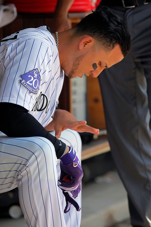 . Colorado Rockies\' Carlos Gonzalez examines his left index finer after attempting to bunt unsuccessfully during the eighth inning of a baseball game against the Arizona Diamondbacks on Wednesday, May 22, 2013 in Denver. The Rockies won 4-1. Gonzalez hurt his left index finger on the play. (AP Photo/Barry Gutierrez)