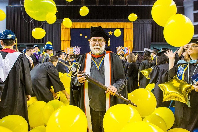 Grand marshal James Begét caries the university mace as he leads the recessional during the 2017 commencement ceremony Saturday, May 6, 2017 at the Carlson Center.