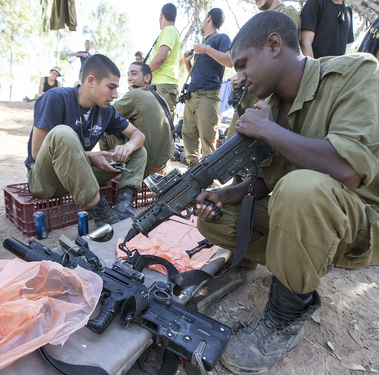 . Israeli soldiers from an Infantry Brigade clean their weapons at an army deployment area near Israel\'s border with the Gaza Strip, on July 16, 2014. New Israeli air and tank strikes in Gaza killed several people, medics said, bringing the death toll from Israel\'s operation in the besieged Palestinian territory to 208. Since the latest violence began before dawn on July 8, 990 rockets fired from Gaza have struck Israel, and another 244 have been shot down by the Iron Dome anti-missile system, army figures show.  AFP PHOTO / JACK GUEZ/AFP/Getty Images