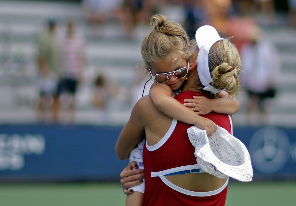 . Larissa Niejelow, 4, hugs Elena Vesnina, of Russia, after Vesnina\'s first round match against Annika Beck of Germany at the 2013 U.S. Open tennis tournament Tuesday, Aug. 27, 2013, in New York. Vesnina defeated Beck 6-1, 6-1. (AP Photo/David Goldman)