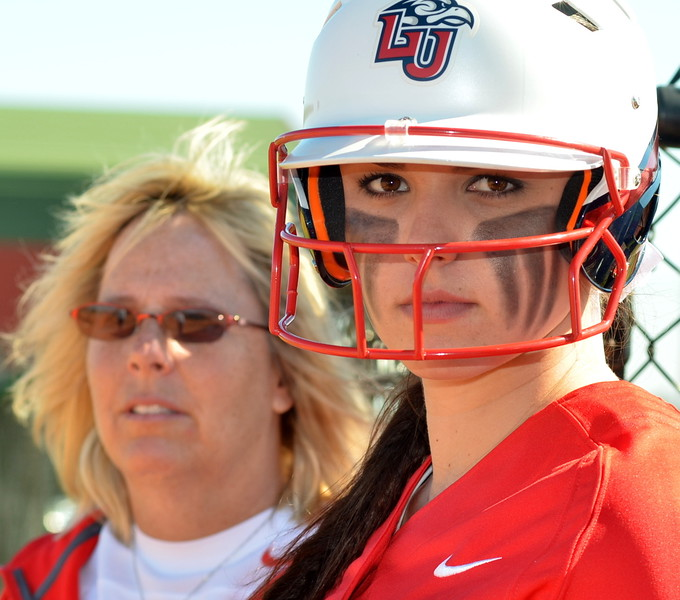 foreground-kaitlin mcfarland,17 year old freshman for the flames out of liberty university is focused in on her next at bat while hall of fame_gold medal olympian dot richardson looks on.JPG