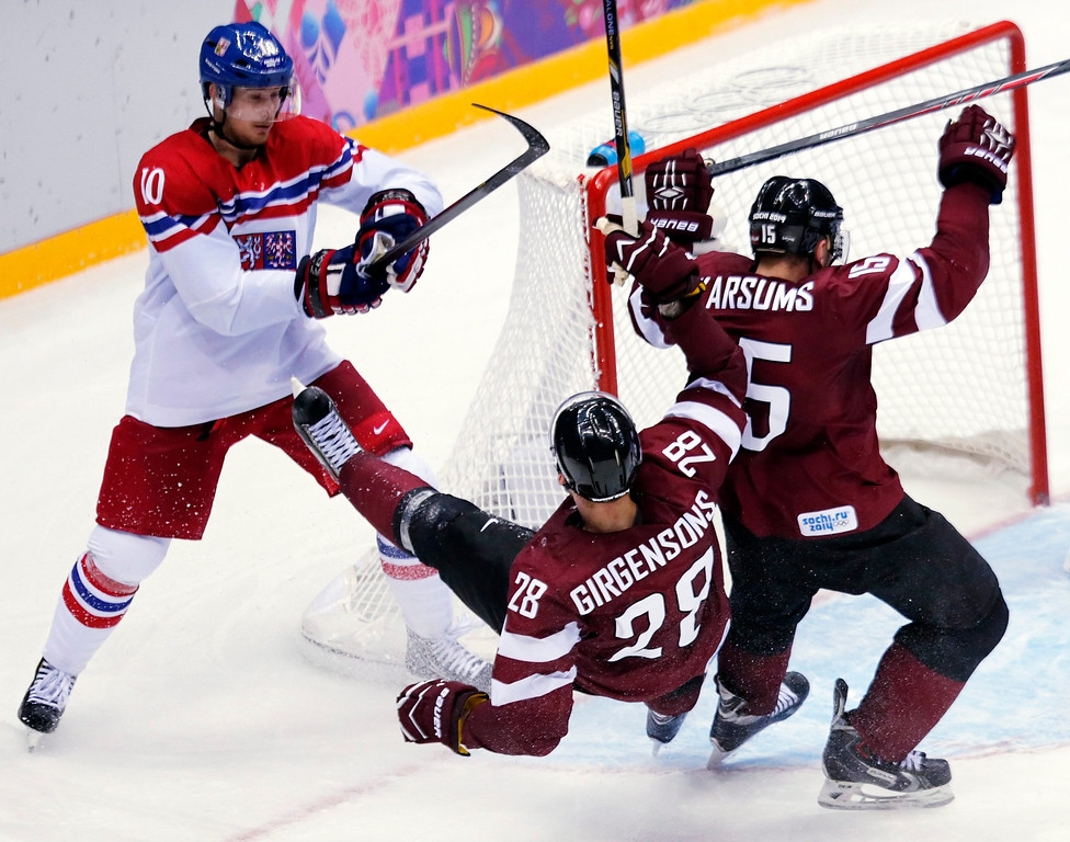 . Roman Cervenka (L) of Czech Republic fights for the puck with Latvia players Zemgus Girgensons (C) and Martins Karsums (R) during the match between Russia and Sweden at the Bolshoy Ice dom in the Ice Hockey tournament at the Sochi 2014 Olympic Games, Sochi, Russia, 14 February 2014.  EPA/ANATOLY MALTSEV