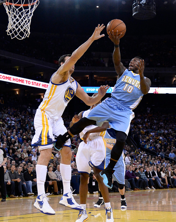 . Denver Nuggets point guard Nate Robinson (R) goes to the basket while getting fouled by Golden State Warriors center Andrew Bogut of Australia (L) during the first half.  EPA/JOHN G. MABANGLO CORBIS OUT