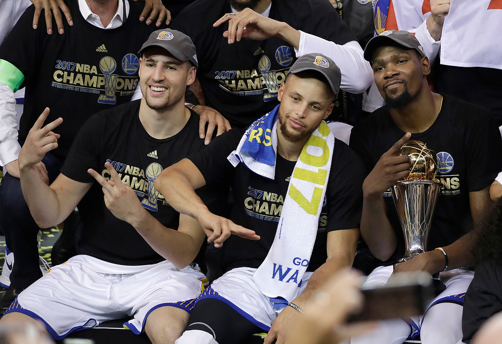 . Golden State Warriors guard Klay Thompson, from left, guard Stephen Curry and forward Kevin Durant celebrate after Game 5 of basketball\'s NBA Finals against the Cleveland Cavaliers in Oakland, Calif., Monday, June 12, 2017. The Warriors won 129-120 to win the NBA championship. (AP Photo/Marcio Jose Sanchez)