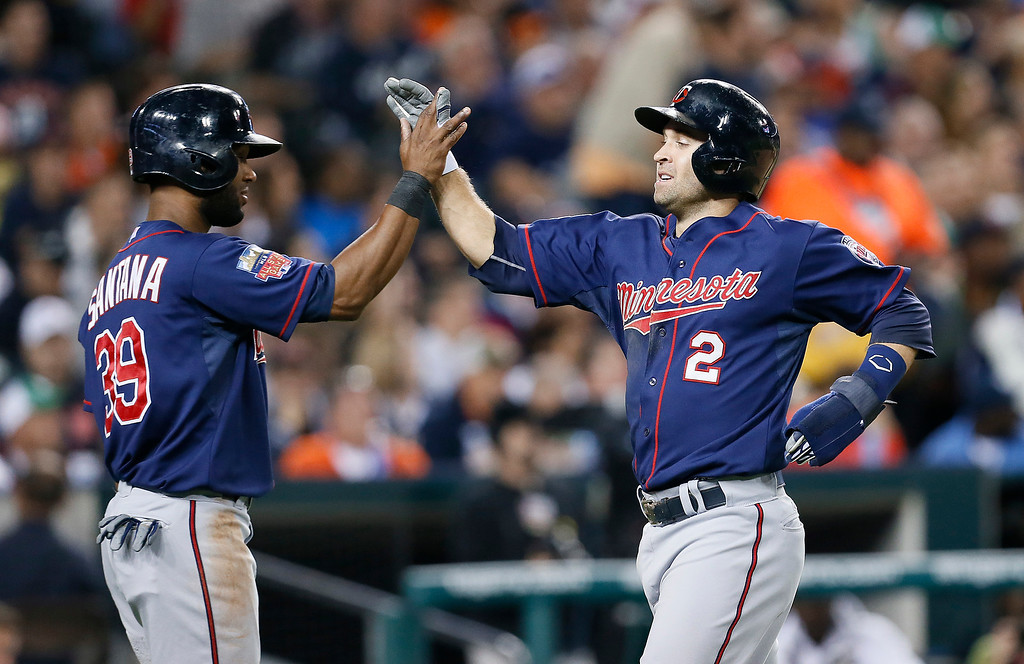 . Minnesota Twins\' Brian Dozier (2) and Danny Santana (39) celebrate after scoring on a Joe Mauer double in the the fifth inning of a baseball game against the Detroit Tigers in Detroit, Thursday, Sept. 25, 2014. (AP Photo/Paul Sancya)
