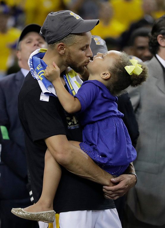 . Golden State Warriors guard Stephen Curry kisses his daughter Riley after Game 5 of basketball\'s NBA Finals between the Warriors and the Cleveland Cavaliers in Oakland, Calif., Monday, June 12, 2017. The Warriors won 129-120 to win the NBA championship. (AP Photo/Marcio Jose Sanchez)