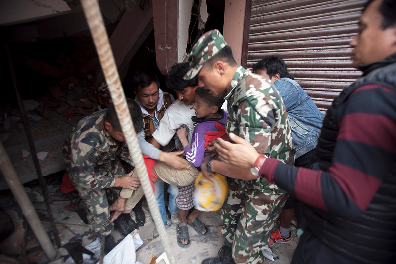 . Volunteers carry an injured boy after rescuing him from the debris of a building that was damaged in an earthquake in Kathmandu, Nepal, Saturday, April 25, 2015. A strong magnitude-7.9 earthquake shook Nepal\'s capital and the densely populated Kathmandu Valley before noon Saturday, causing extensive damage with toppled walls and collapsed buildings, officials said. (AP Photo/ Niranjan Shrestha)