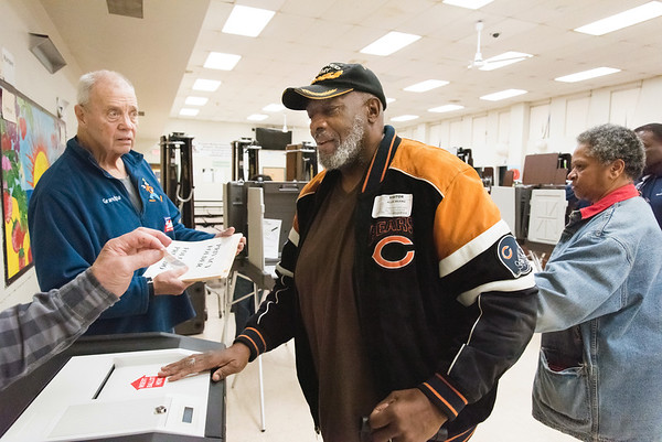 11/06/18 Wesley Bunnell | Staff Tabulation Tender Carl Symecko, L, looks on as Allen Wilkins receives his I Voted sticker from fellow Tabulation Tender Gus Prisco at the Pulaski Middle School voting location on Tuesday afternoon.