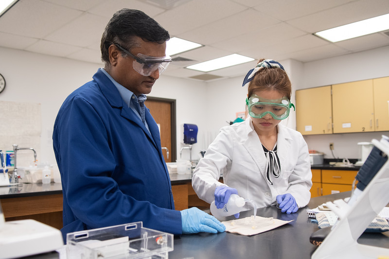 Professor Navendra Narayana (left) assists Nga Tran in applying water to assure that there is no leakage on the slate tray.