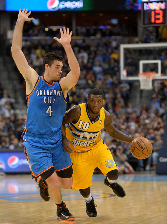 . Denver Nuggets point guard Nate Robinson (10) drives on Oklahoma City Thunder power forward Nick Collison (4) during the second quarter December 17, 2013 at Pepsi Center. (Photo by John Leyba/The Denver Post)