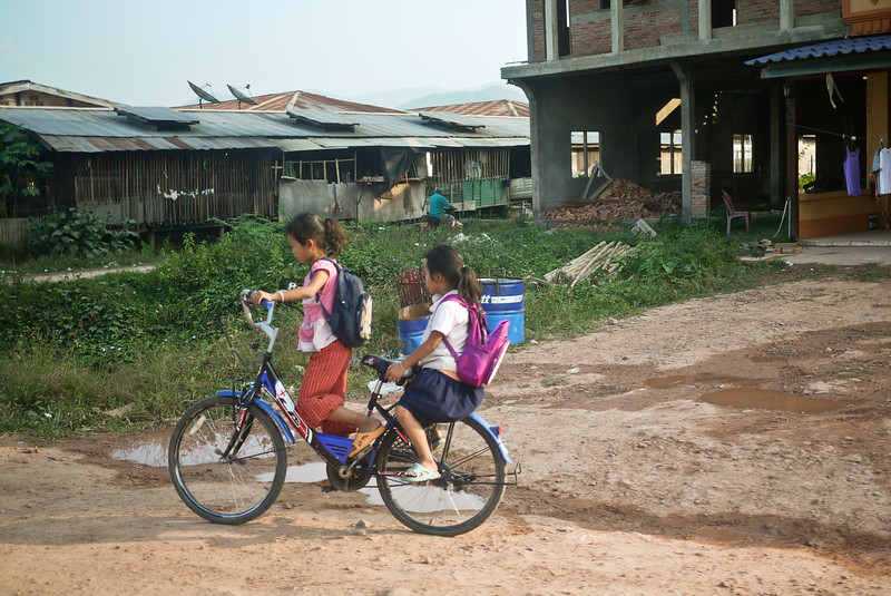 Two little girls make their way home from school in Hongsa, Laos.