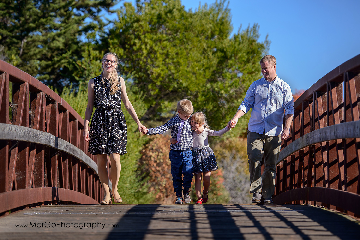 family of 4 holding hands and walking on the bridge at Mountain View Shoreline Lake Park