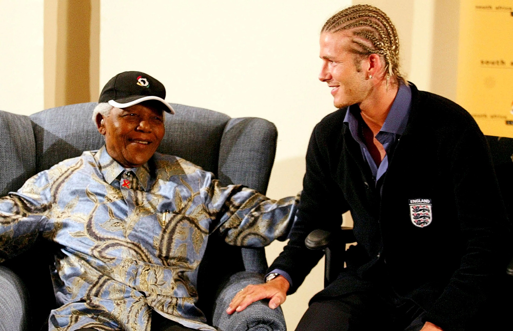 . Former South African President Nelson Mandela chats with England\'s soccer captain David Beckham at the Nelson Mandela Foundation office in Johannesburg, in this file picture taken May 21, 2003. REUTERS/Juda Ngwenya/Files