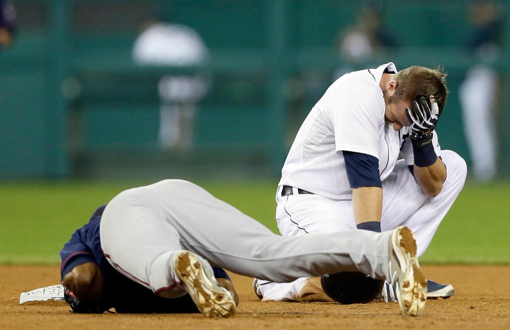 . Detroit Tigers\' Andrew Romine holds his head after receiving a hit by Minnesota Twins shortstop Danny Santana\'s right knee on a force out hit into by Detroit Tigers\' Ian Kinsler during the seventh inning of a baseball game in Detroit, Saturday, Sept. 27, 2014. (AP Photo/Carlos Osorio)