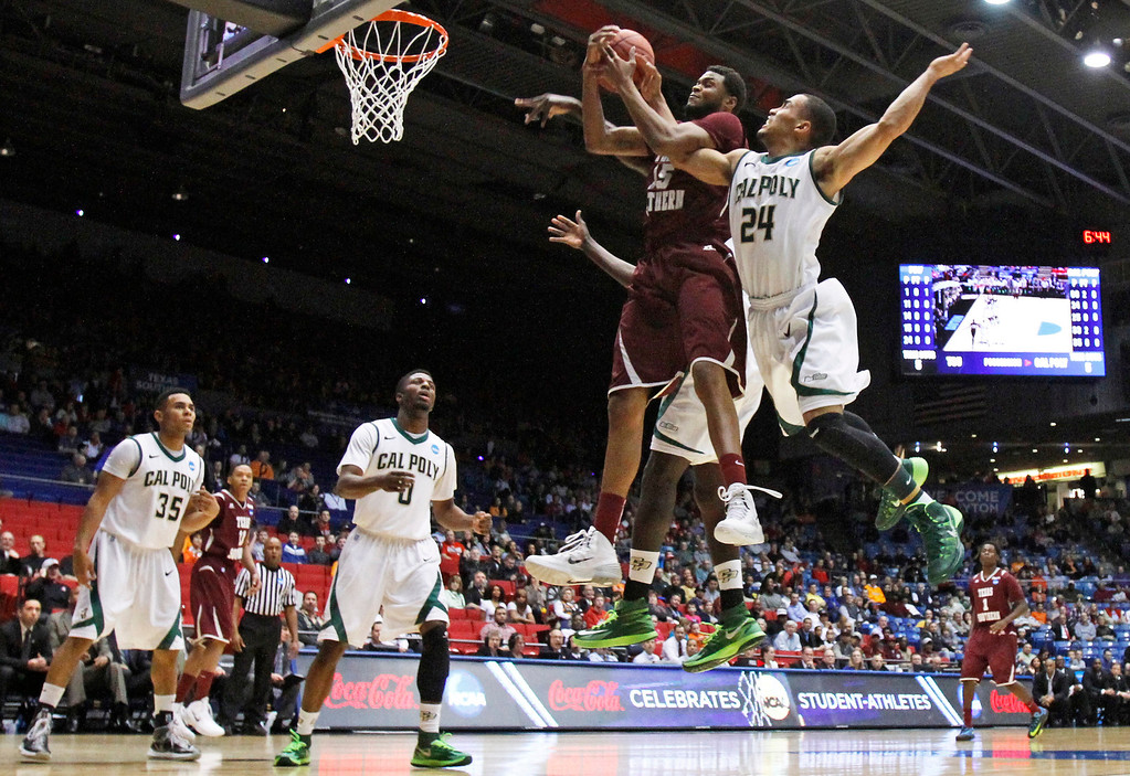 . Texas Southern forward D\'Angelo Scott (15) goes up for a rebound against Cal Poly guard Jamal Johnson (24) in the first half of a first-round game of the NCAA college basketball tournament on Wednesday, March 19, 2014, in Dayton, Ohio. (AP Photo/Skip Peterson)