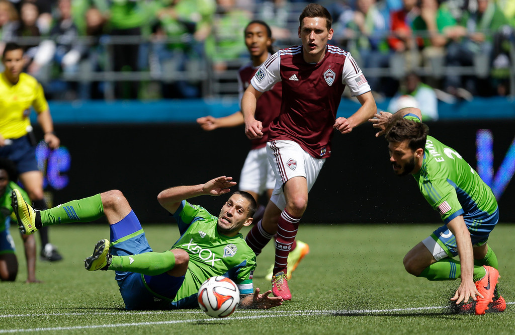 . Seattle Sounders\' Clint Dempsey, left, and Brad Evans, right, go down during a play against Colorado Rapids\' Shane O\'Neill, center, in the second half of an MLS soccer match, Saturday, April 26, 2014, in Seattle. The Sounders defeated the Rapids, 4-1. (AP Photo/Ted S. Warren)