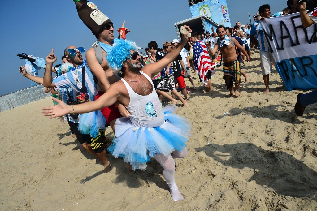 . Fans dance at the FanFest at Copacabana beach in Rio de Janeiro as they gather to watch a live projection of the round of 16 football match between Argentina and Switzerland during the 2014 FIFA World Cup on July 1, 2014. AFP PHOTO / GIUSEPPE CACACE/AFP/Getty Images