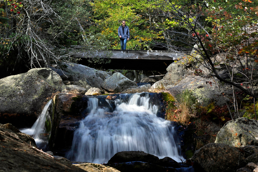 . In this Thursday, Sept. 28, 2017 photo a hiker walks out on a bridge to view a waterfall at the Crystal Cascades in Pinkham Notch, N.H. Despite forecasts for brilliant foliage throughout the Northeast this year, long-time leaf watchers say the leaves this fall are dull and weeks behind schedule in their turn from green to the brilliant hues of autumn. (AP Photo/Robert F. Bukaty)