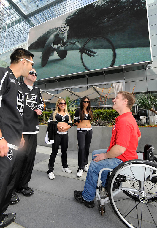 """. Ryan Chalmers talks to members of the LA Kings Ice Crew outside the JW Marriott at LA Live. Chalmers is pushing himself in a wheel chair on a coast-to-coast trip that starts at the JW Marriott in Los Angeles, and will end in New York\'s Central Park. The 3000 mile odysey will raise funds for an organization called  \""""Stay Focused\"""" that allows teens and young adults with disabilities to participate in sports alongsid able-bodied people.  Los Angeles CA 4/6/2013(John McCoy/Staff Photographer"""