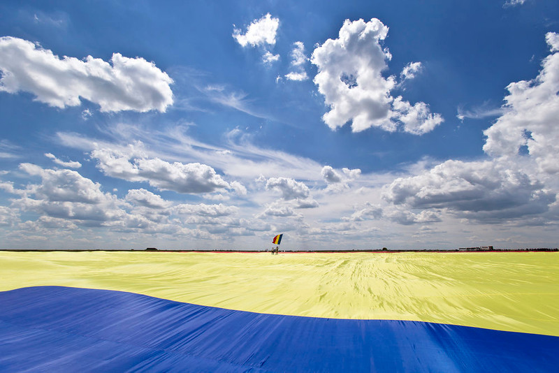 . A man holding a Romanian flag stands on a record breaking version of the flag, on the Clinceni Airfield, south of Bucharest,  Romania, Monday, May 27, 2013. Romania entered the Guinness Book of records after it unveiled the largest flag ever made. It took about 200 people several hours Monday to unfurl a five-ton flag of Romania which organizers said measured 349.4 meters by 226.9 meters, about three times the size of a football pitch.(AP Photo/Vadim Ghirda)