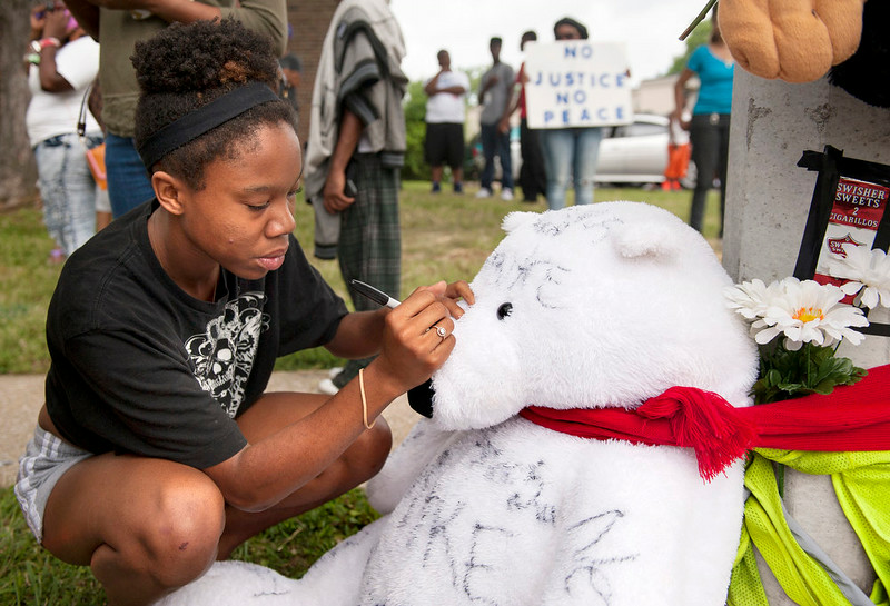 . Piaget Crenshaw adds a message to items left at a spontaneous memorial for shooting victim Michael Brown, 18, Sunday, Aug. 10, 2014 at the scene of the shooting in Ferguson, Mo. Brown died following a confrontation with police, according to St. Louis County Police Chief Jon Belmar, who spoke at a news conference Sunday. Crenshaw, who lives in the apartment complex where Brown was shot, said she was a witness. (AP Photo/Sid Hastings)