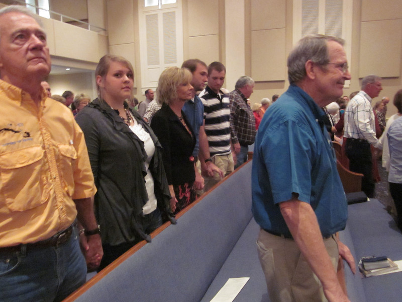 2011 10-15  Charlie Park, executive director of Fuller Center Webster, attends worship service at First Baptist Minden with arriving volunteers. The pastor had the group go to the front so that members of the church could have laying on of hands and pray for the upcoming week.