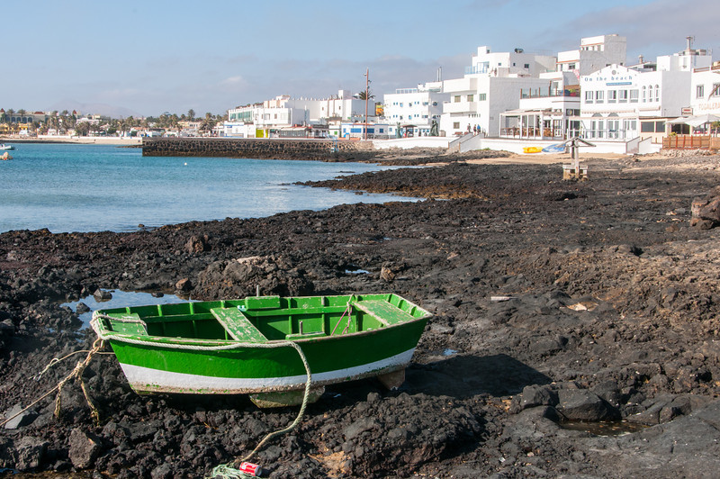 Solitary boat along rocky beach in Corralejo, Fuerteventura, Spain