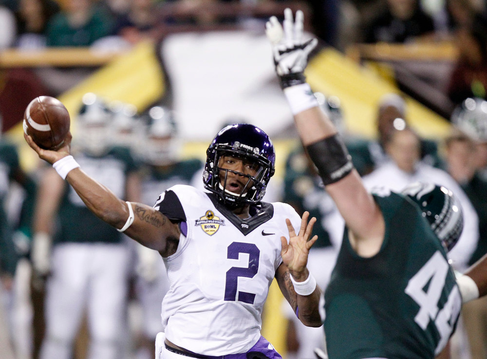 Description of . TCU quarterback Trevone Boykin, left, passes under pressure from Michigan State defensive end Marcus Rush, right, during the first half of the Buffalo Wild Wings Bowl NCAA college football game Saturday, Dec. 29, 2012, in Tempe, Ariz. (AP Photo/Paul Connors)