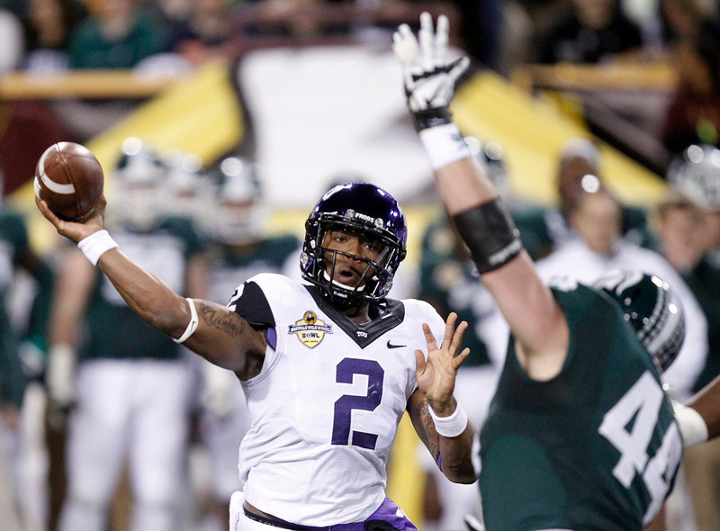 . TCU quarterback Trevone Boykin, left, passes under pressure from Michigan State defensive end Marcus Rush, right, during the first half of the Buffalo Wild Wings Bowl NCAA college football game Saturday, Dec. 29, 2012, in Tempe, Ariz. (AP Photo/Paul Connors)