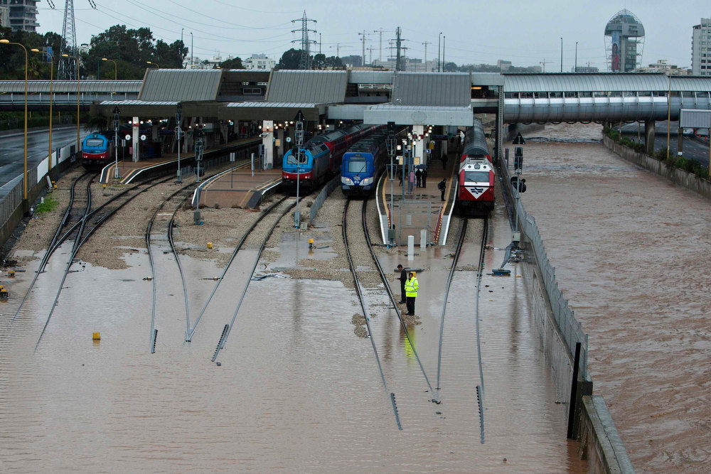 Description of . Railway workers stand at a flooded train station in Tel Aviv January 8, 2013. Unusually heavy winter rains forced the closure of main access routes to Tel Aviv on Tuesday, causing gridlock in and around Israel's commercial capital, authorities said. Traffic backed up for hours as highways into Tel Aviv were flooded, police said. Rail operator asked commuters to avoid stations in the city and train schedules were disrupted. REUTERS'/Nir Elias