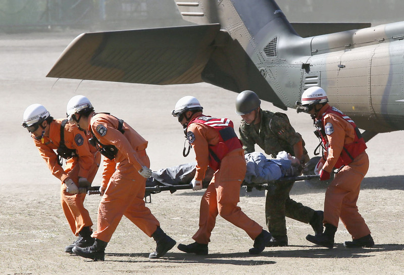 . Rescue workers carry a climber rescued from Mount Ontake into an ambulance, in Kiso, Nagano prefecture in central Japan, Sunday, Sept. 28, 2014. Mount Ontake erupted shortly before noon Saturday, spewing large white plumes of gas and ash high into the sky and blanketing the surrounding area in ash. Rescue workers have found 30 or more people unconscious and believed to be dead near the peak of an erupting volcano in central Japan, local government and police said. (AP Photo/Kyodo News)