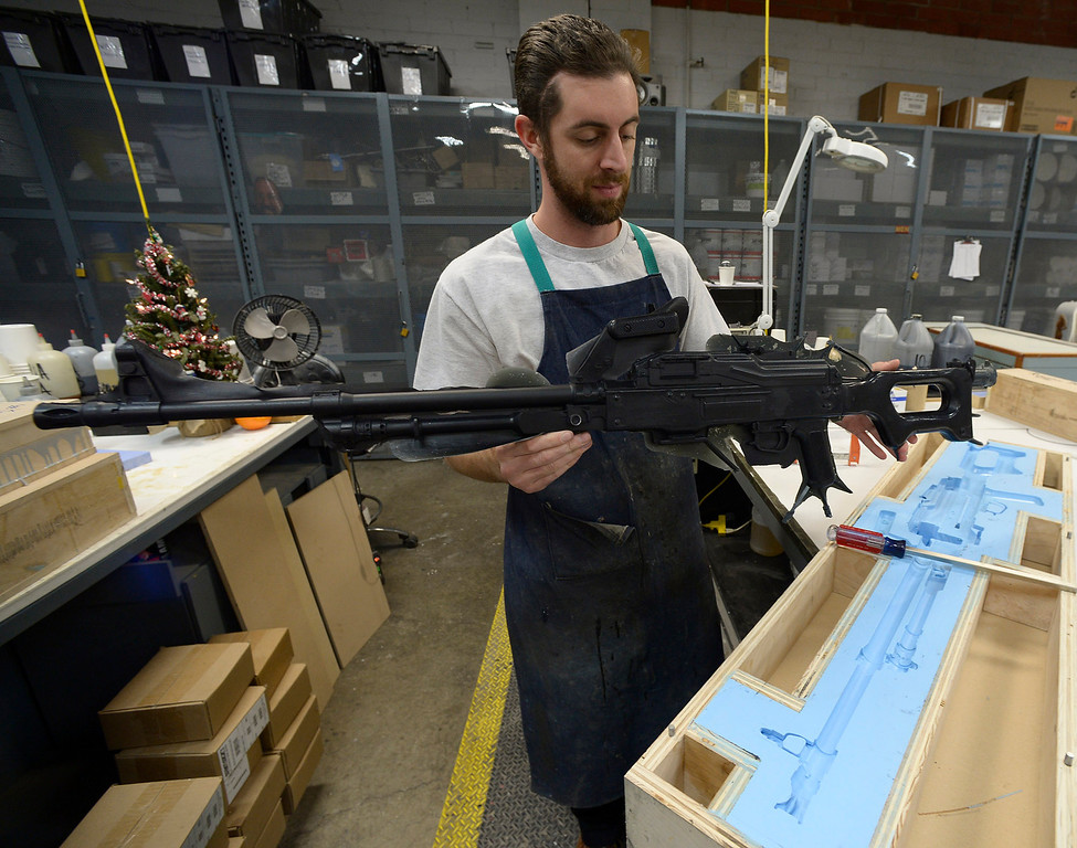 . Matt Tilley looks over a freshly minted PKM assault rifle that he modes out of rubber. Tilley works for Gregg Bilson, Jr. the CEO of ISS Independent Studio Services, a prop house that holds hundreds of thousands of items used for motion pictures and television production. Runaway production has an impact on his business. Sunland, CA 12-31-2013. photo by (John McCoy/Los Angeles Daily News)