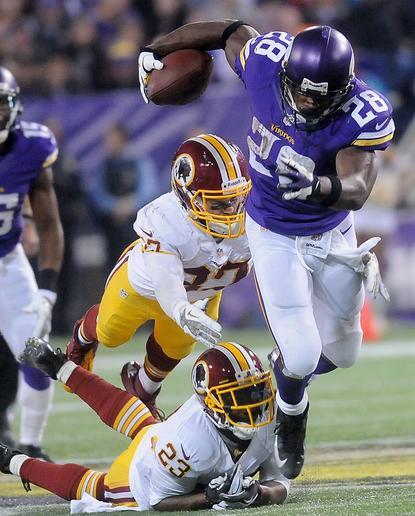 . Minnesota Vikings running back Adrian Peterson escapes the grasp of Washington cornerback DeAngelo Hall and teammate strong safety Reed Doughty during the fourth quarter. (Pioneer Press: Sherri LaRose-Chiglo)