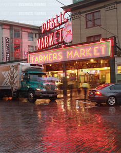 Pike Place Public Market in Seattle glows in red neon at sunrise as vendors setup their stands for the start of the business day