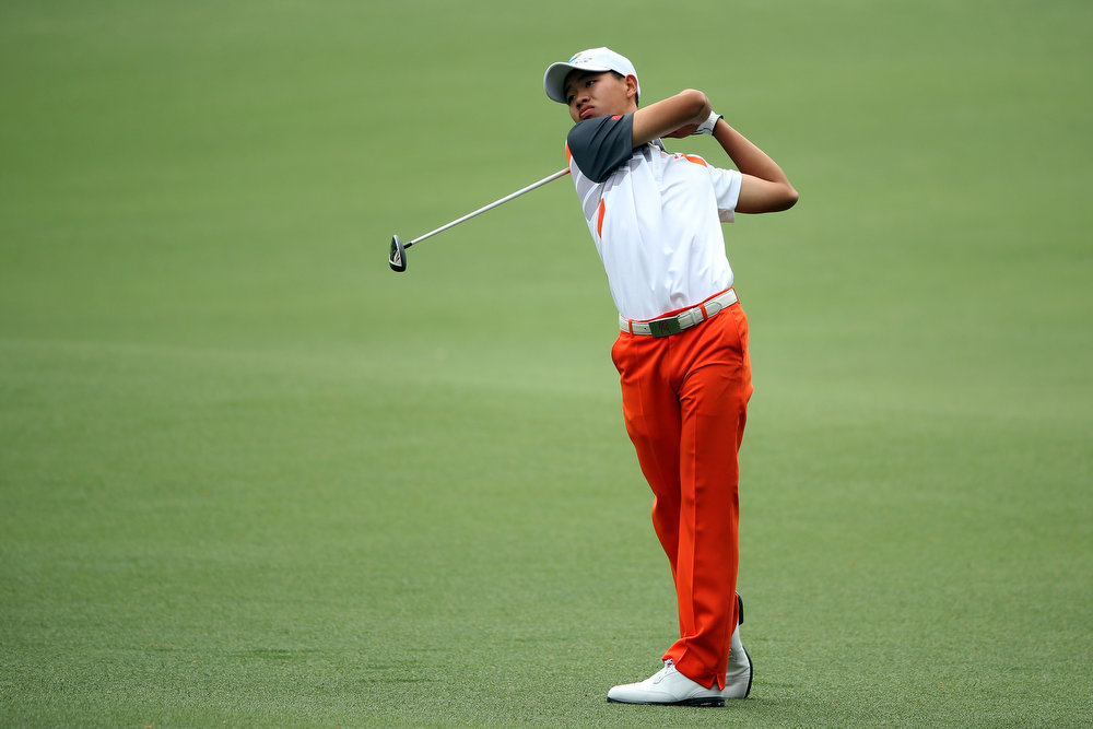 Description of . Tianlang Guan of China hits his second shot on the 8th hole during the final round of the 2013 Masters Tournament at Augusta National Golf Club on April 14, 2013 in Augusta, Georgia.  (Photo by Andrew Redington/Getty Images)