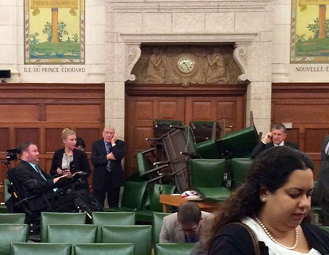 . In this photo provided by Conservative MP Nina Grewal, members of Parliament barricade themselves in a meeting room on Parliament Hill in Ottawa, Canada, Wednesday, Oct. 22, 2014, after shots were fired in the building. (AP Photo/The Canadian Press, Nina Grewal)